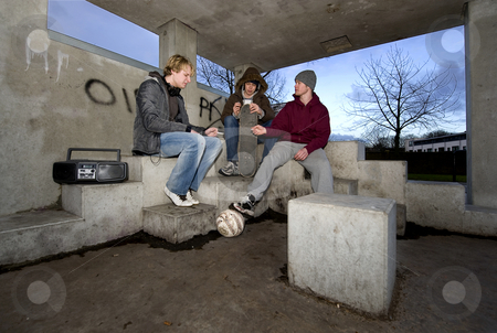 Smoking shelter stock photo, Three adolescent youths lighing cigarettes in a shelter in a suburbian area by Corepics VOF