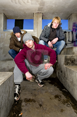 Suburban gang stock photo, Three angry looking gangmembers in a dirty, concrete bunker at dusk. by Corepics VOF