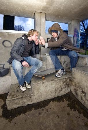 Smoking shelter stock photo, Two adolescent youths in a suburbian area, lighting a cigarette in a concrete shelter, hanging out by Corepics VOF