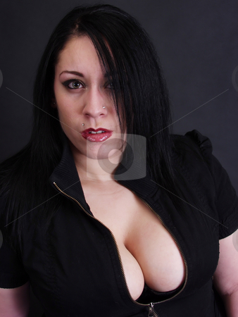 Seriously stock photo, A pierced female in black goth style clothes gives a dumbfounded look. Over black by Robert Gebbie