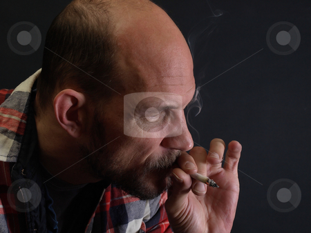 Smoking Man stock photo, A man in a plaid shirt smokes a cigarette over a black background. by Robert Gebbie