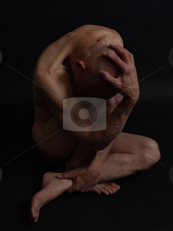 Twisted stock photo, A bald nude male sits twisted and knotted, his head in his hand. Over a black background. by Robert Gebbie