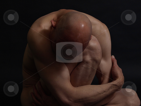 Depression Hits stock photo, A clean shaven nude male sits in darkness, crumpled up. Over a black background. by Robert Gebbie