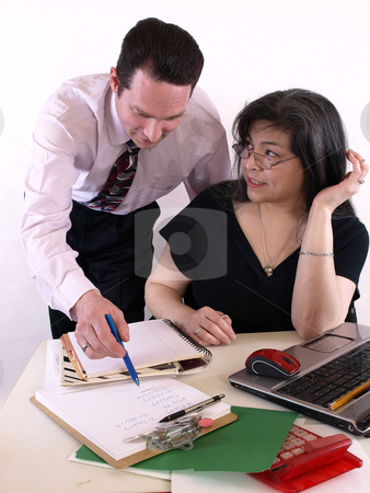 Working on a Project stock photo, A male and female working together in the office at the computer. Isolated against a white background. by Robert Gebbie
