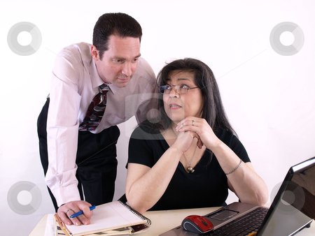 Business Couple at Computer stock photo, A male and female working together in the office at the computer. Isolated against a white background. by Robert Gebbie