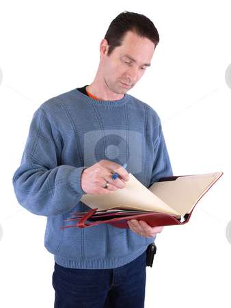 Turns the Page stock photo, An adult male looking over notes in a binder, isolated against a white background. by Robert Gebbie