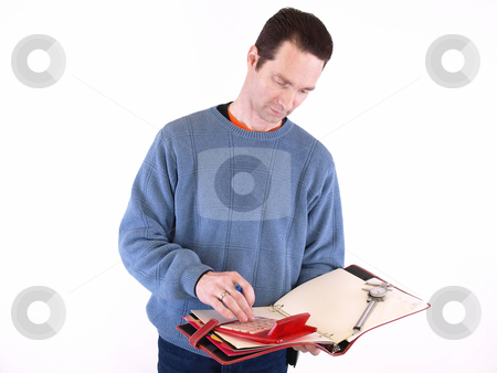 Calculating Measurements stock photo, An adult male in blue checks over some measurements in a binder. Isolated on a white background. by Robert Gebbie