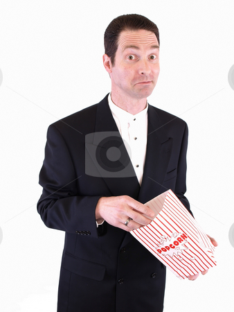 Caught Chewing stock photo, A white male in a suit puts his hand into a popcorn bag. He is chewing on something in his mouth. by Robert Gebbie