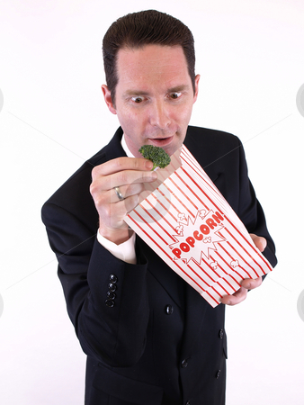 Broccoli Surprise stock photo, A man in a black suit pulls a piece of broccoli from a popcorn bag. Over white. by Robert Gebbie