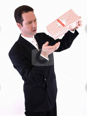 All Out stock photo, A white male in a suit shakes a bag of popcorn into his hand.  He is frustrated because there is no more. by Robert Gebbie