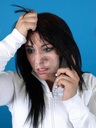 Bad News on the Phone stock photo, Alternative style adult woman looks stressed as she speaks into the telephone. by Robert Gebbie