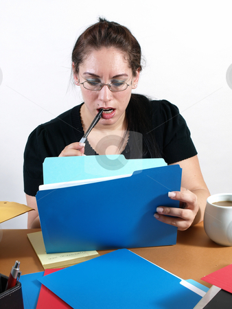 Secretary Checking Files stock photo, A female office worker checks a file with a pen to her lips. by Robert Gebbie