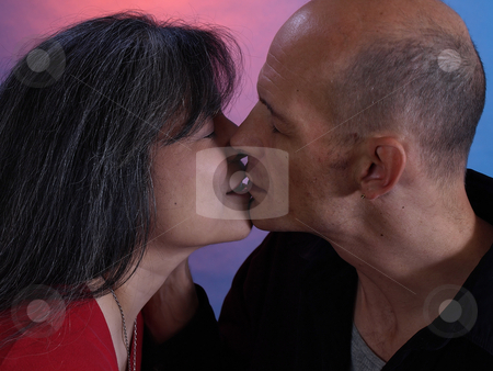 Kisses stock photo, An older man and woman lean in for a gentle kiss. by Robert Gebbie