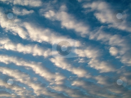 Plowed Clouds stock photo, These clouds look as if someone plowed them into brilliant white puffy rows as they are set off by one of the bluest of winter skies. This type of altocumulus undulatus clouds are normally the result of a sudden directional or speed shift in the wind. by Krystal McCammon