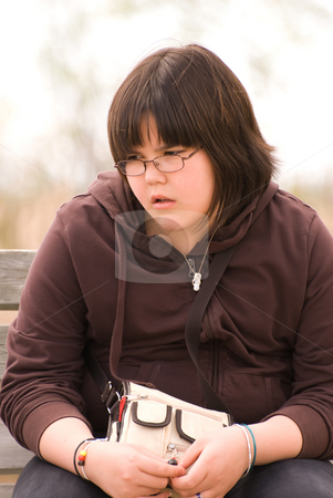 Bored Child stock photo, A young girl sitting outside with a bored or depressed look on her face by Richard Nelson