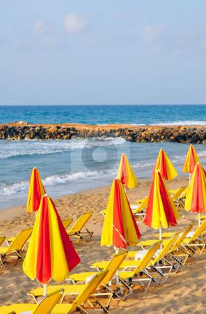 Sunbeds and umbrellas stock photo, Summer: sunbeds and umbrellas in mediterranean beach by Fernando Barozza