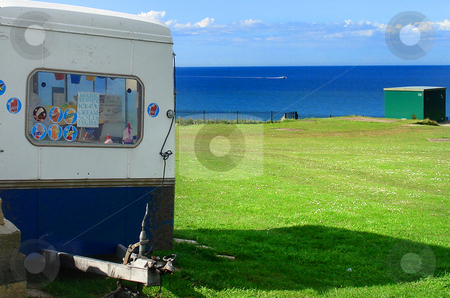 Ice cream van stock photo, Greem grass field, cloudy blue sky ocean and Ice cream van. by Marc Torrell