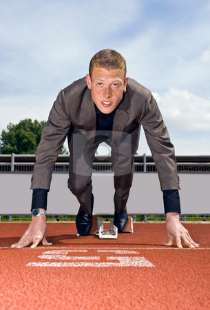 Ready to build a career stock photo, Young businessman wearing a suit in the starting blocks to start building his career by Corepics VOF