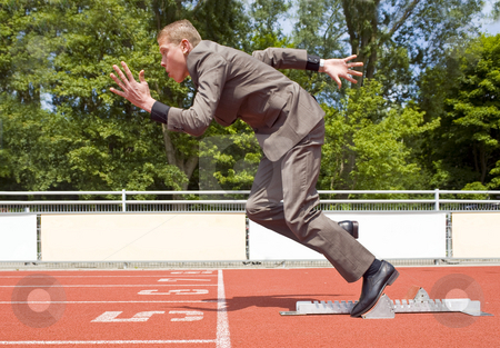 Career start stock photo, Young businessman explosively surging out of the starting blocks of his career by Corepics VOF
