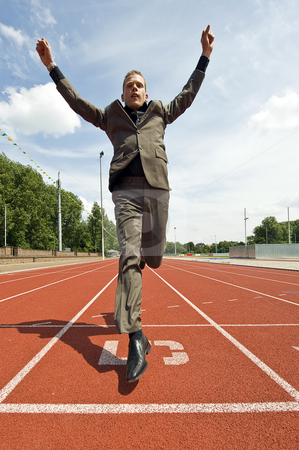 Success in Business stock photo, Metaphore for success in business - a business man crossing the finish line on an athletics track with his arms raised in victory by Corepics VOF