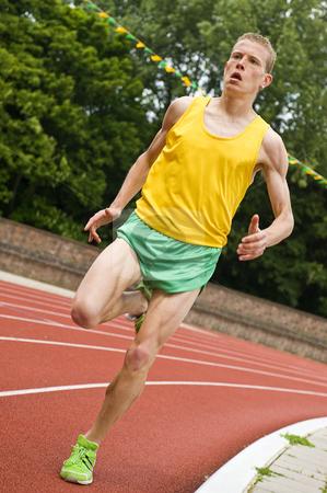 Running stock photo, Athlete running a middle distance race on an oval track by Corepics VOF