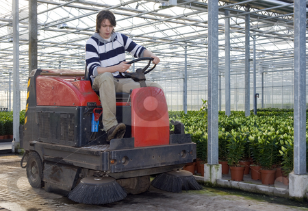 Cleaning a glasshouse stock photo, A man on an industrial cleaning machine, cleaning the concrete floor of a glasshouse by Corepics VOF
