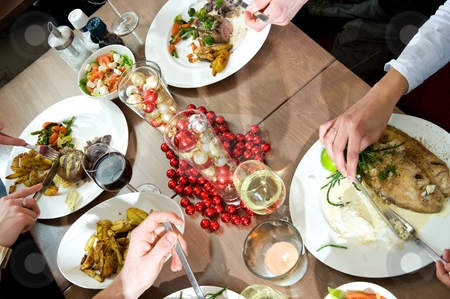 Christmas dinner stock photo, Meals being eaten on a restaurant table decorated for christmas by Corepics VOF