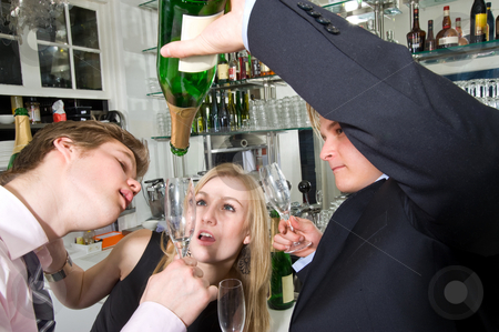 Taking the last drop of champagne stock photo, Three young, drunken adults taking the last drop of champagne at a bar by Corepics VOF