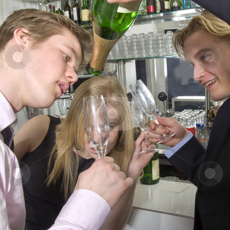 Taking the last drop of champagne stock photo, Three drunken persons taking the last drop of champagne at a bar by Corepics VOF