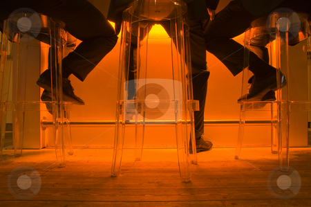 Businessmen on bar stools stock photo, The legs of three businessmen on bar stools, sitting behind an orange lit bar on transparent plastic stools on a wooden floor by Corepics VOF