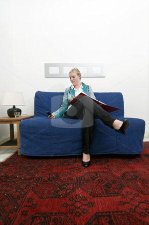 Working at home stock photo, A business woman working at home going over a dossier on a couch by Corepics VOF