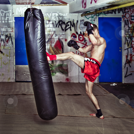 Forward kick stock photo, Muay Thai fighter giving a forceful forward kick during a practise round with a boxing bag by Corepics VOF