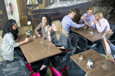 Restaurant setting stock photo, Overview of a crowded bar with various groups of people sitting at tables waiting for their orders by Corepics VOF