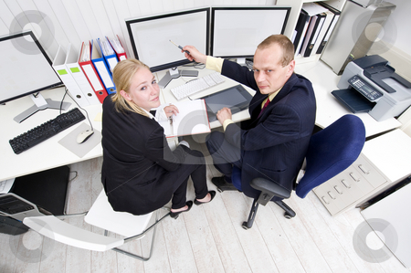 Cooperating colleagues stock photo, Two colleagues cooperating behind a dual flatscreen monitor by Corepics VOF