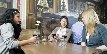 Girl talk stock photo, Three women gossiping at a restaurant table over a glass of wine by Corepics VOF