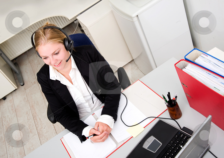 Friendly receptionist stock photo, Friendly receptionist on the phone wearing a headset and microphone by Corepics VOF