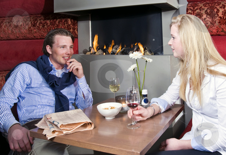 Intimate talk stock photo, Young upper-class couple talking by the fireplace by Corepics VOF