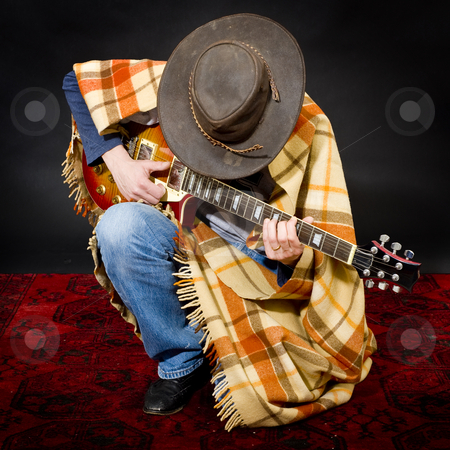 Blues rock stock photo, Blues rock parody with a manin shabby clothes playing the guitar by Corepics VOF
