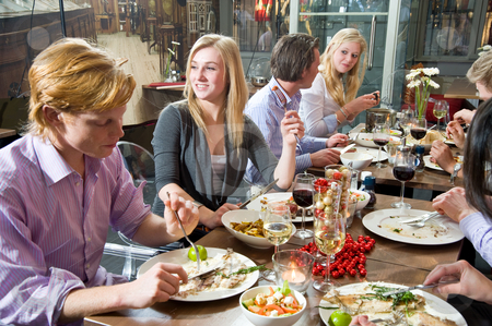 Dinnertime stock photo, Group of people enjoying a rich dinner in a restaurant by Corepics VOF