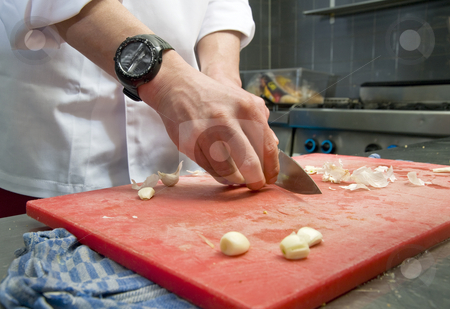 Cutting Garlic stock photo, A chef cutting garlic in a professional kitchen by Corepics VOF