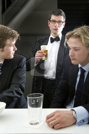 At the Bar stock photo, Three men at the bar of a cafe, dressed in formal clothes by Corepics VOF