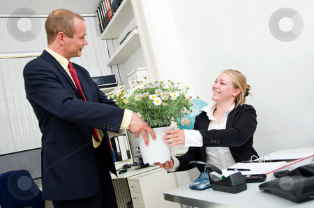 Colleague friendship stock photo, Senior manager giving his younger female associate a large flower pot with white daisies by Corepics VOF