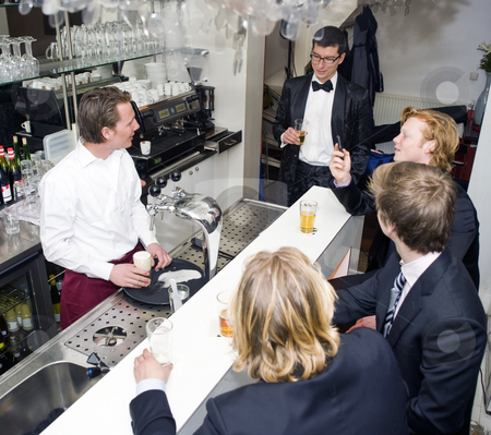 Bar stock photo, Four customers around a bar, being served by a barman by Corepics VOF