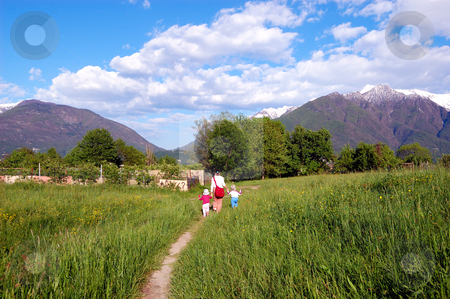 Family Walking in spring field stock photo, Family Walking in spring field by ALESSANDRO TERMIGNONE
