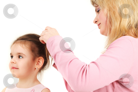 Mother helping daughter  stock photo, Portrait of mother helping daughter with hair, studio shot by Tom P.
