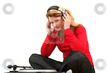 Young woman listening to record  stock photo, Portrait of young woman listening to record with headphones, studio shot by Tom P.