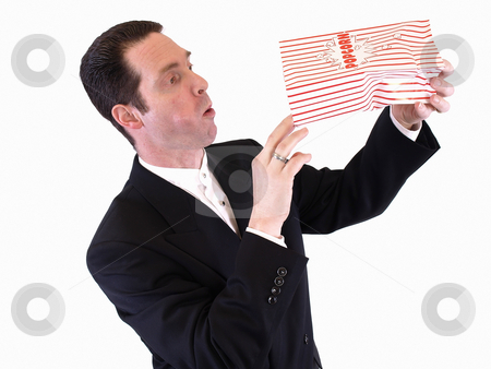 Wanting More Popcorn stock photo, A white male in a suit tips a bag of popcorn, peeking in.  His mouth is full. by Robert Gebbie