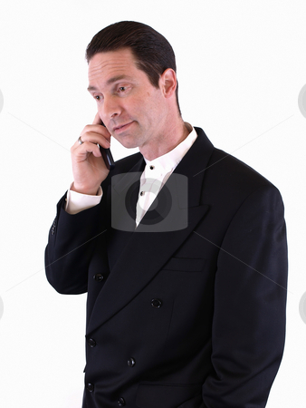 Taking a Call stock photo, A man in a black suit takes a phone call on his cell.  Isolated over white. by Robert Gebbie