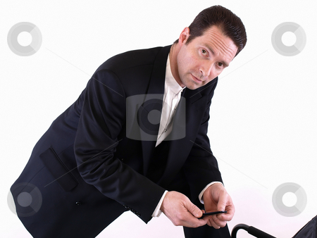 Man with Cell Phone stock photo, A standing man leans down on one knee to check an incoming text message on his cell phone. by Robert Gebbie