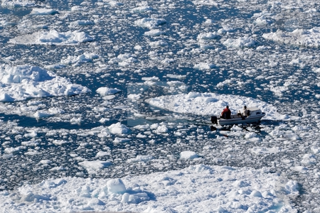 Boat in icefield stock photo, Motorboat going through an icefield in Ilulissat, Greenland by Anders Peter